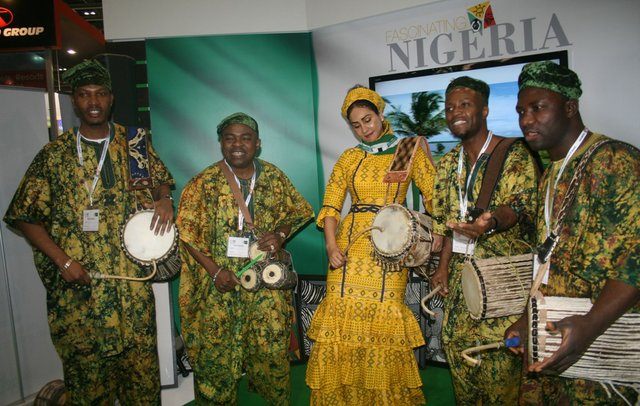 Mrs. Sally Mbanefo with the Oduduwa  Talking Drummers - Ayan De First in Europe entertaining guests at the stand.