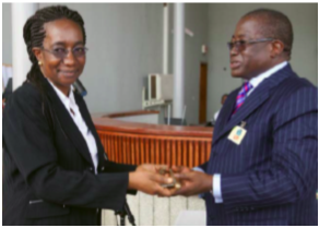 Registrar Binta Mansaray presents an over-sized ceremonial key to Sierra Leone's Attorney-General and Minister of Justice Franklyn Bai Kargbo
