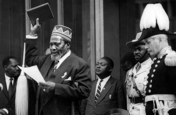 Jomo Kenyatta takes the oath during his swearing-in as Kenya's first Prime Minister on June 1, 1963. On his right is Governor Malcolm Macdonald.