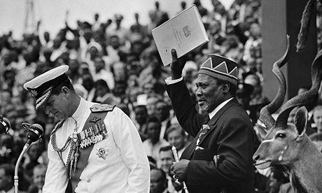 Kenyan former leader Jomo Kenyatta pictured with the official document of independence in Nairobi on 13 December 1963