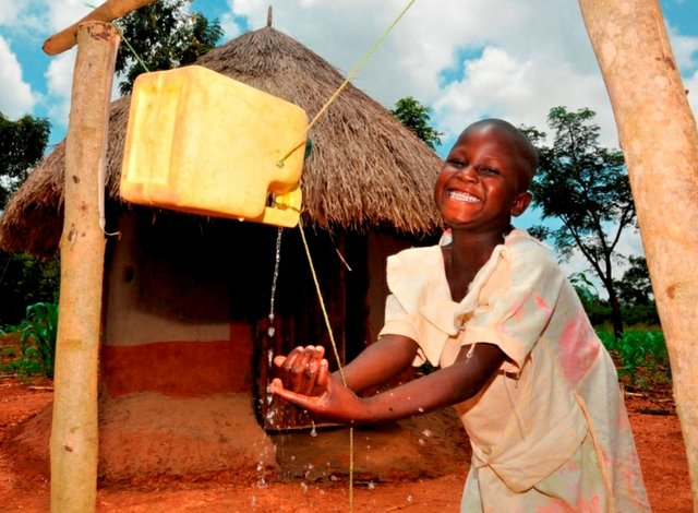 A girl washes her hands using a 'Tippy Tap' – which encourages safer handwashing practices – outside her family's clean pit latrine in Busia, Uganda.
