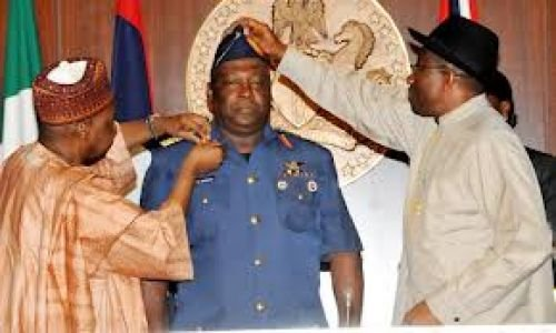 Air Vice Marshal being decorated by President Jonathan, assisted by Vice President Namadi Sambo