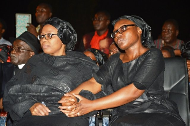 Komla's wife Kwamsema (left) and sister Mawuena (right) holding hands during the ceremony