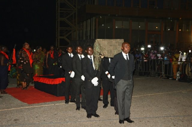 Pallbearers taking Komla's casket away after the ceremony