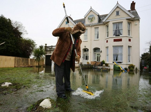 Kye Gbangbola clearing floodwater from his front garden in January