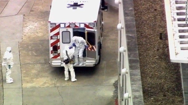 Dr. Kent Brantly, right, gets out of an ambulance after arriving at Emory University Hospital in Atlanta.jpg