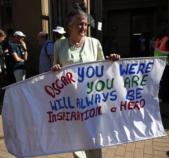 A woman holds a banner in support of Pistorius