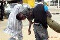 An injured man being helped by volunteers