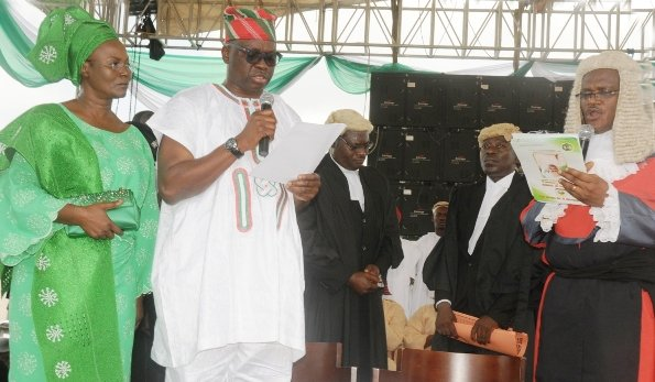 The new Governor of Ekiti State - Ayodele Fayose in the company of his wife taking the Oath of Office being administered by the State's Chief Judge - Justice Ayodeji Daramola