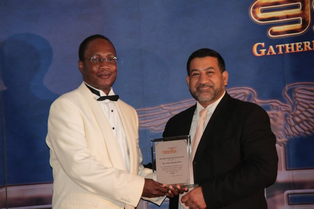 Channels TV's Koye Shotade (left) receives GAB Award on behalf of Channels TV Chairman - John Momoh from Peter Mudalhy.jpg