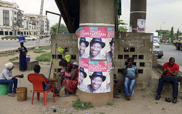 Workers sit beside campaign posters of Nigerian President and presidential candidate Goodluck Jonathan in Lagos (Photo - Pius Utomi Ekpei / AFP)