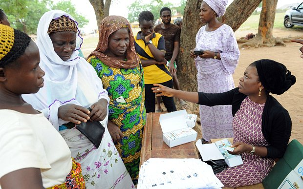 Women wait to collect their Permanent Voter Cards at Shimaw, southwestern Nigeria (AFP)