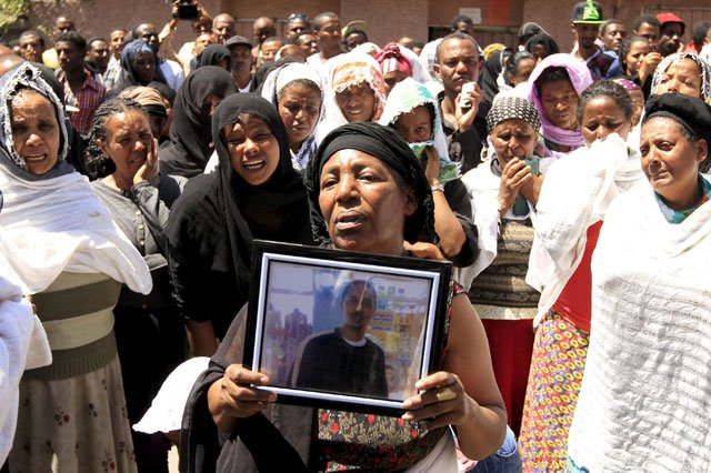 A woman mourns with the framed picture of a man said to be among the 30 Ethiopian victims killed by Daesh militants in Addis Ababa