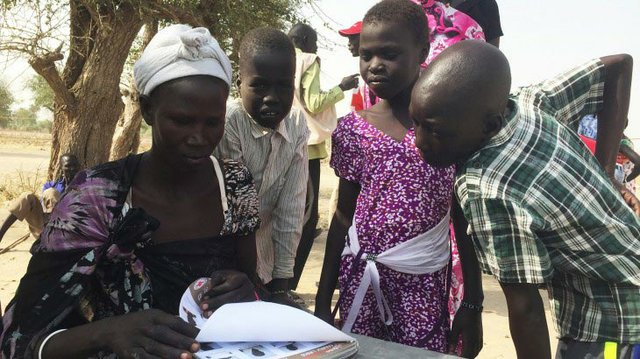 A group of people in Leer review a book containing photos of South Sudanese children located in the neighbouring countries