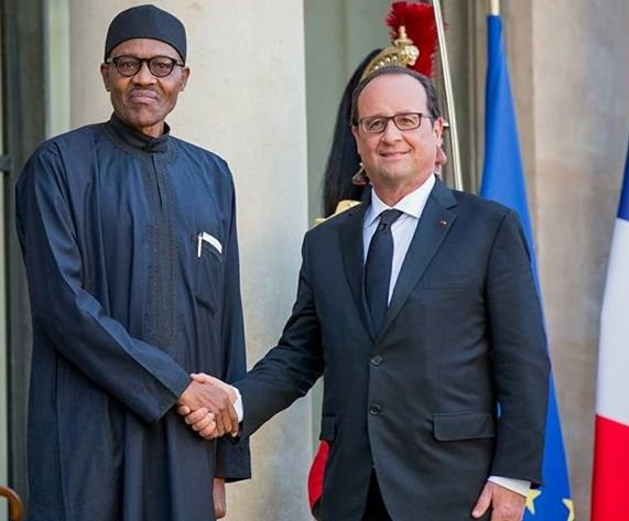 Nigeria's President Muhammadu Buhari in a warm handshake with France's President Francoise Hollande at Elysee Palace