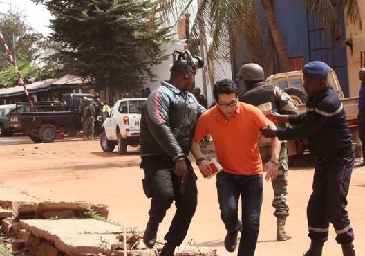 Troops assist a hostage to leave Radisson Blu hotel  in Bamako to safety