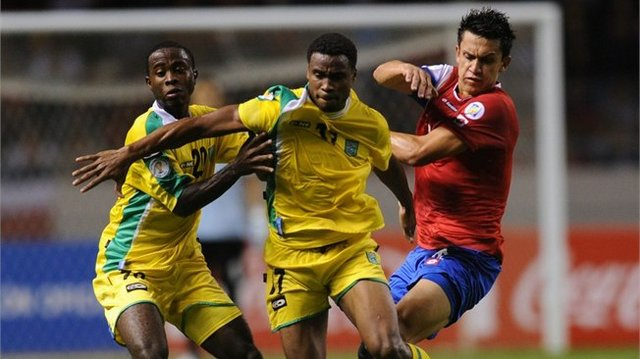 Guyana's players Treyon Bobb (L) and Vurlon Mills (C) vie for the ball with Costa Rican Jose Luis Cordero