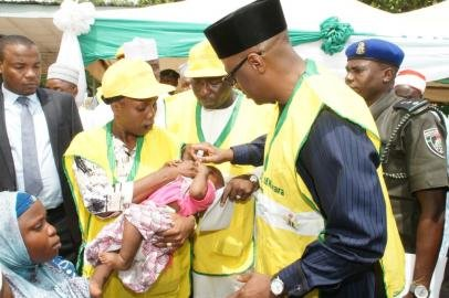 Kwara State Governor - Dr Abdulfatah Ahmed (right), administering polio vaccine on a child while the