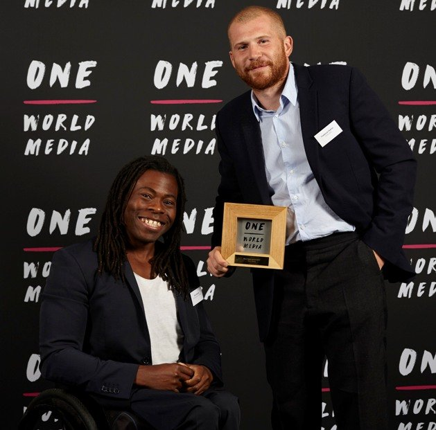 Frederick Paxton collecting the New Voice Award on behalf of May Jeong with presnenter Ade Adepitan at the One World Media Awards