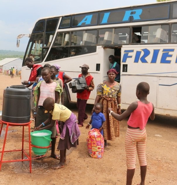 South Sudanese children washing their hands after getting off the bus. About 2,000 refugees cross into Uganda every day
