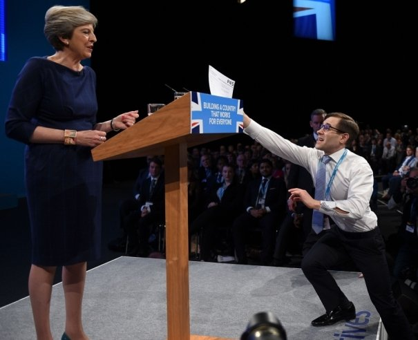 Simon Brodkin a.k.a Lee Nelson hands Thresa May a P45