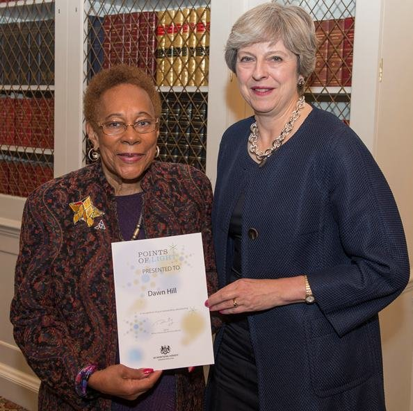 Prime Minister Theresa May presents a Point Of Light award to Dawn Hill, Chair of the Black Cultural Archives in Brixton