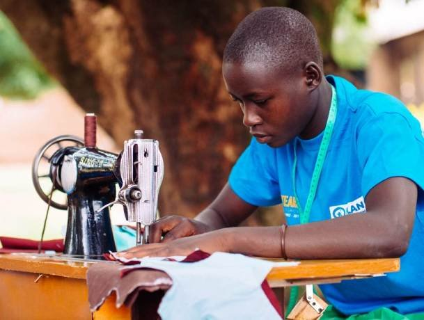 A boy sews a reusable sanitary towel at a menstrual hygiene club in eastern Uganda