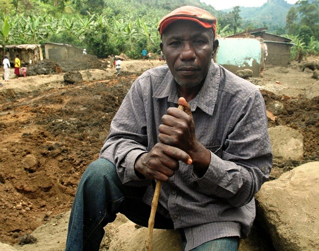 Lawrance Khisa seated in the boulders at Wangemen trading centre which was completely destroyed