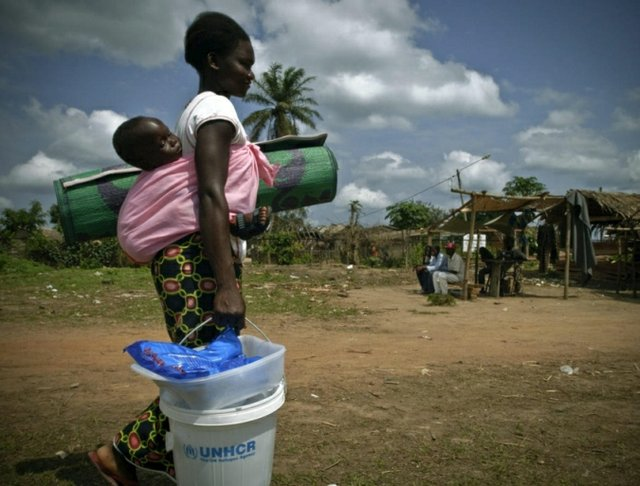 A refugee mother carries her child and relief items in Congo-Brazzaville.