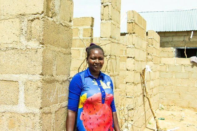 Faraa stands in front of the house she has started building with proceeds from her pasta business, a few meters away from the host community that welcomed her in Yola