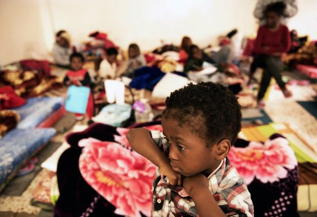 A child stands in a room where women and children sleep on old mattresses laid on the floor at a detention centre in Libya