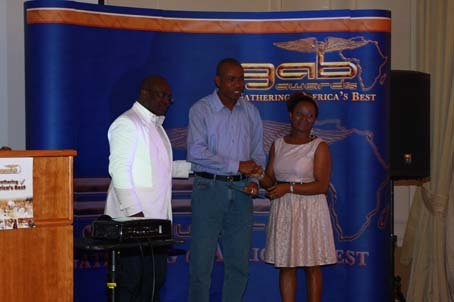Mr Segun Oyebolu (middle) receiving his award from Mr Dele and Mrs Esther Ogun.JPG