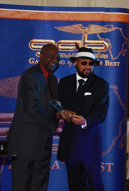 Sunny Lambe receiving his award from Lloyd Honeyghan.JPG