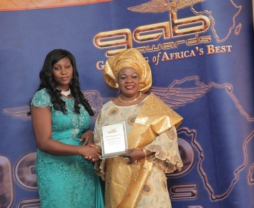 Gloria Olubusola Rowland receiving her award from TV Presenter - Yemi Akande