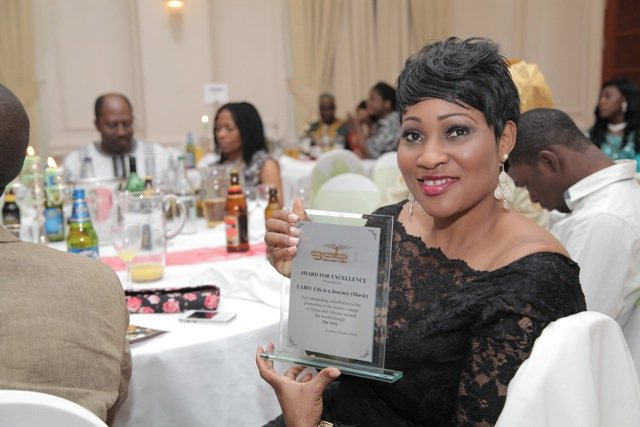 Producer of 'LABO - Life Is A Journey' - Roseline Sanni-Ajose shwos off the award won by the film